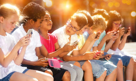 Smiling children sitting at urban street with mobile devices