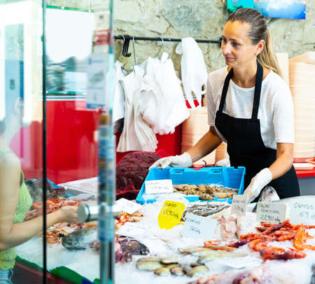 Adult seller offering seafood to female
