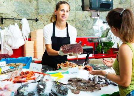 saleswoman offering fresh raw tuna steak to woman