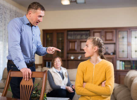 Woman and man lecturing teenage girl