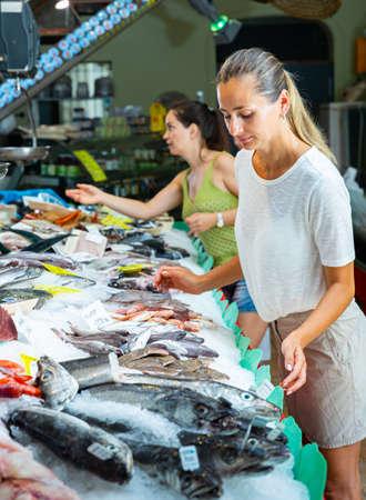 Female customers choosing seafoods at store