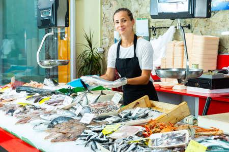 Smiling female fishmonger offering fresh sea bass