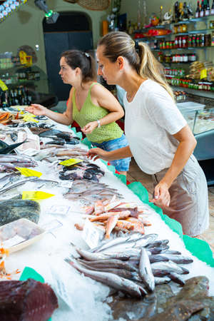 Women looking for seafood on market