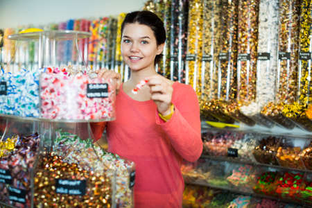 girl buying candies at shop