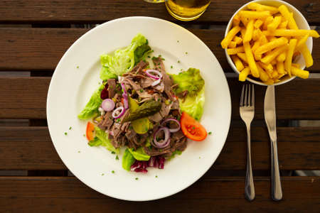 Salad with vegetables, boiled beef and pickled cucumbers