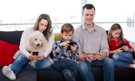 Happy family members spending time playing with smartphones Stock fotó