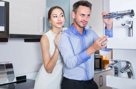 Young man and woman are choosing new mixer tap