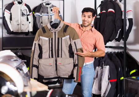 Man is demonstrating new jacket for motorbike in the store.