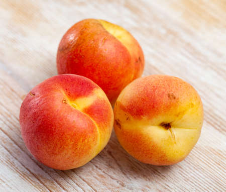 Whole and half fresh apricots on wooden table Imagens