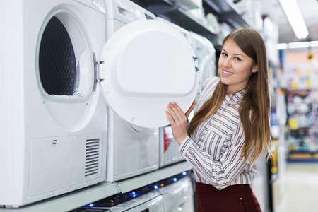 Woman choosing washing machine in household appliances shop