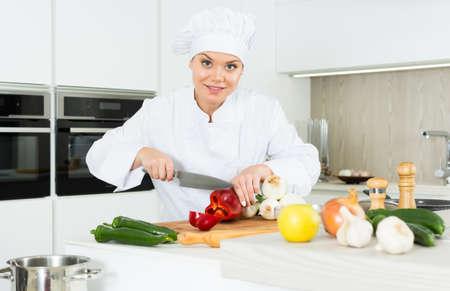 Young woman cook preparing vegetables in white uniform Foto de archivo