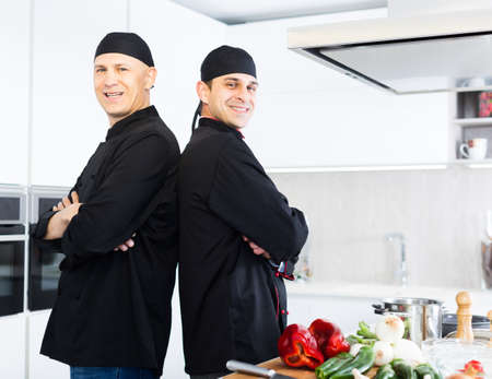 Young male chefs in black uniform standing near workplace