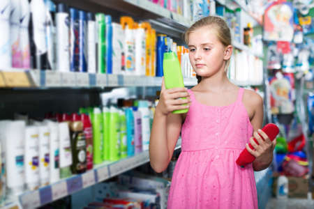 Young girl holding shampoo and conditioner in shop Banco de Imagens