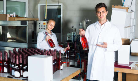 Two young colleagues holding bottles of wine
