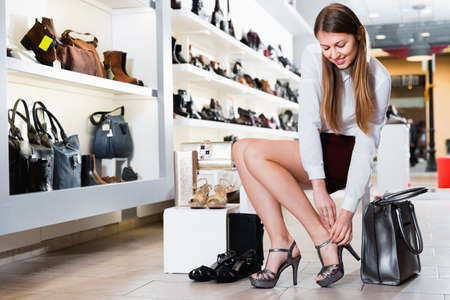 Young female is choosing summer shoes in shoes shop. Imagens