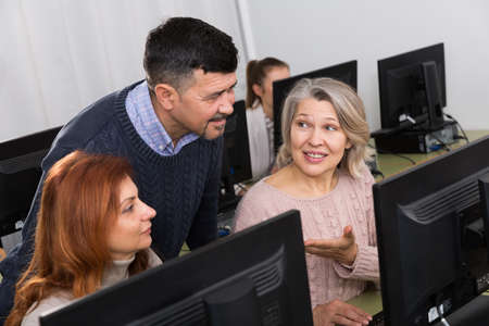 Young and mature coworkers working around computer monitor