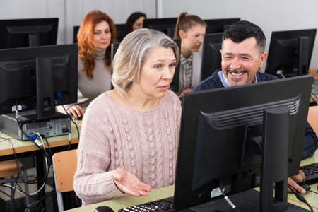 Middle aged man helping woman to use computer