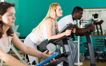 Man and women exercising on stationary bikes Reklamní fotografie