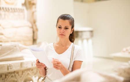 Woman observing sculptures exposition in art museum Imagens