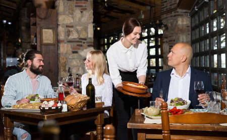 Female owner of rustic restaurant serving guests Banque d'images