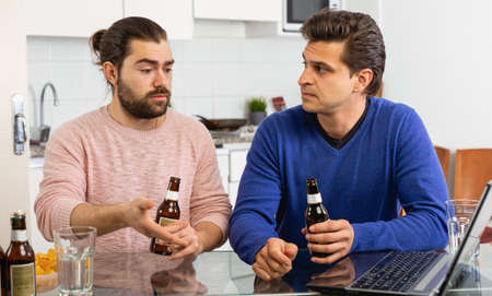 Smiling men sitting at table and drinking beer indoor Imagens
