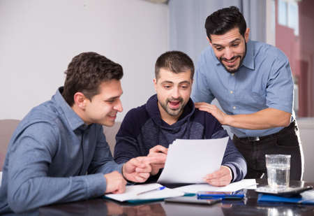 Three cheerful men reading documents at table