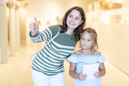 Woman visitor with daughter looking at exhibition in museum Imagens