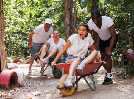 Competitions in amusement park - who will quickly bring girl in the garden wheelbarrow