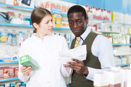 Professional woman pharmacist helping man client with prescription Stockfoto