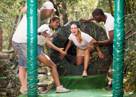 Friends help each other overcome an obstacle course Imagens