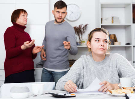 Frustrated woman with papers and discontented family
