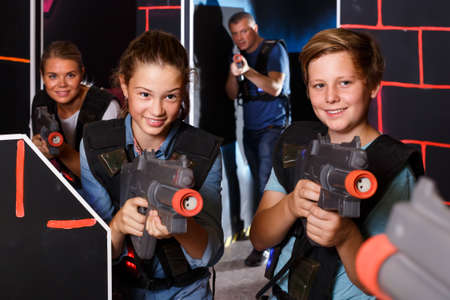cheerful teen brother and sister with laser pistols playing laser tag with their parents