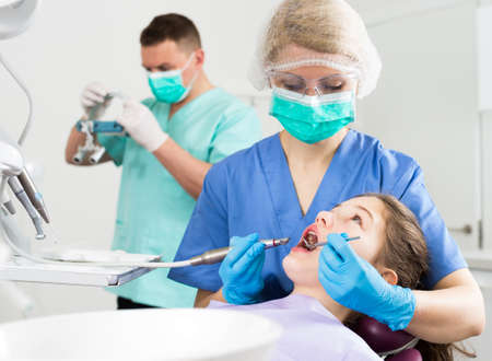 Female dentist treating girl patient with male assistant