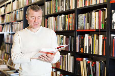 Man browsing inside of books while visiting library Zdjęcie Seryjne