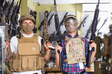 Young guys in military equipment with rifle in airsoft shop