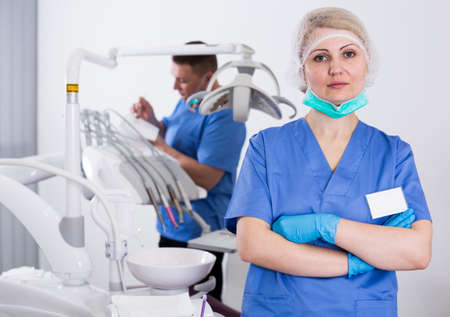Woman dentist in office with assistant