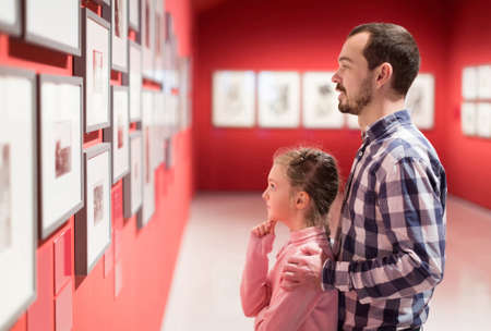 father and daughter looking at exhibition of photos in museum Archivio Fotografico