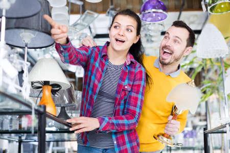 Smiling man and girl choose modern lamp