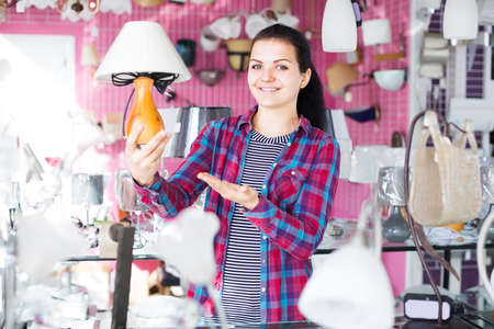 Female customer decided to buy a table lamp