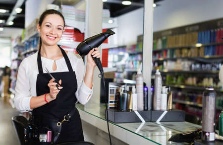 Young woman hairstylist holding blow dryer and hair cutters in cosmetics salon