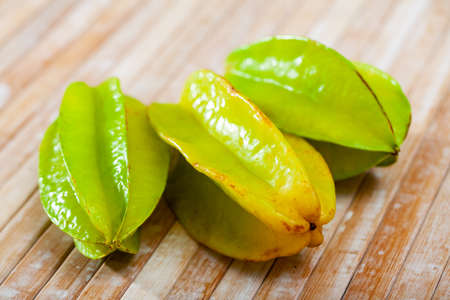 Whole and sliced fruits fresh carambola on table. Healthy vegetarian ingredient