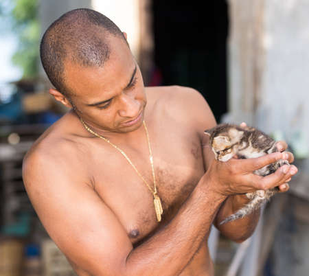 Kind man holds little kitten in his arms