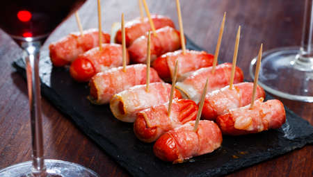 Rolled bacon with sausages on black dish