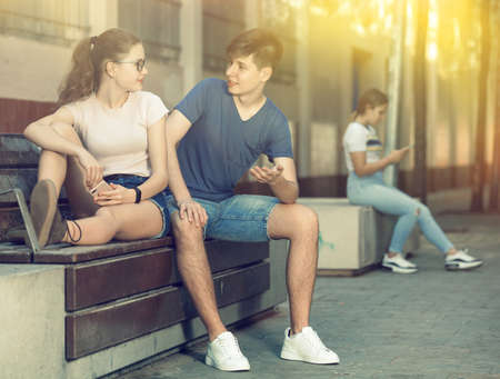 Teenager boy talking with girl on bench on summer day 免版税图像