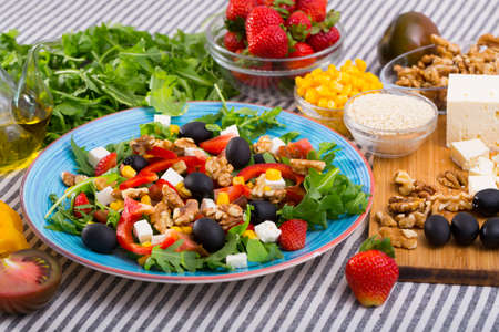 Salad with arugula, olives, Feta cheese, corn and walnut and its ingredients Stock Photo