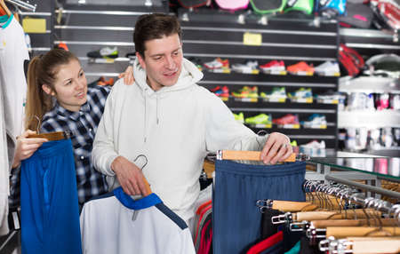 Couple is choosing new tennis shorts in store