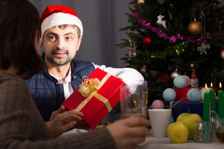 Man in hat giving present to woman at New Year dinner
