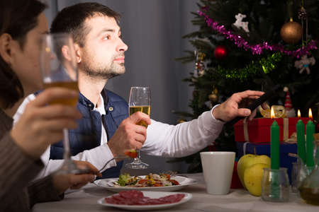 Family celebrate the New Year with champagne and watching tv