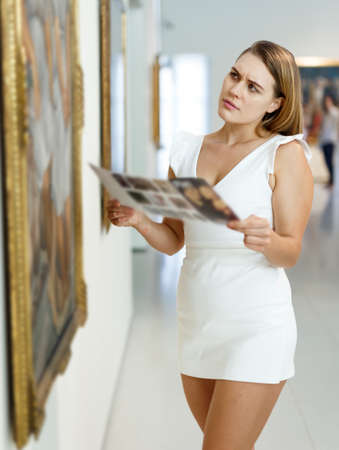Woman visiting painting exhibition