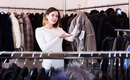 Pretty girl customer examining sheepskin coat Banque d'images